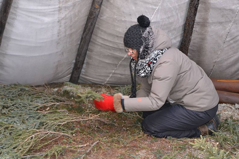 "Roxane Campeau lays a floor branches for the ""mitchuap"" (walking-out) ceremony."